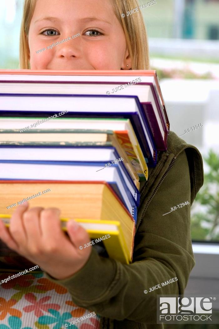 Stock Photo: Girl 7-9 with pile of books, portrait.