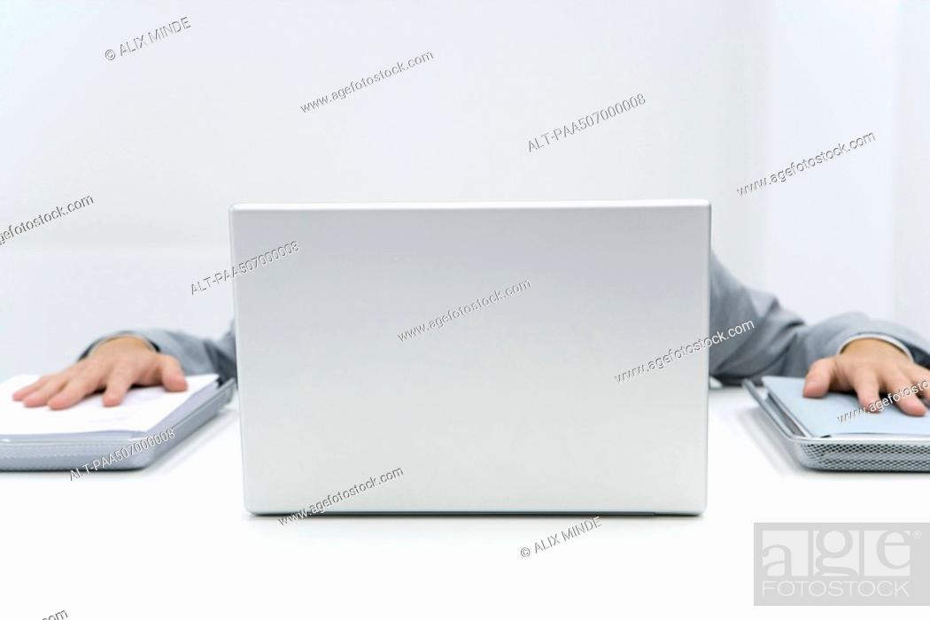 Stock Photo: Man hiding laptop putting palms on stacks of paper to either side.