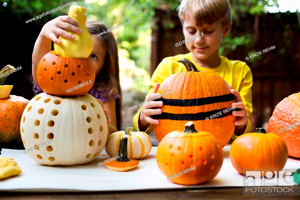 Stock Photo: Girl and brother stacking carved pumpkins on garden table.
