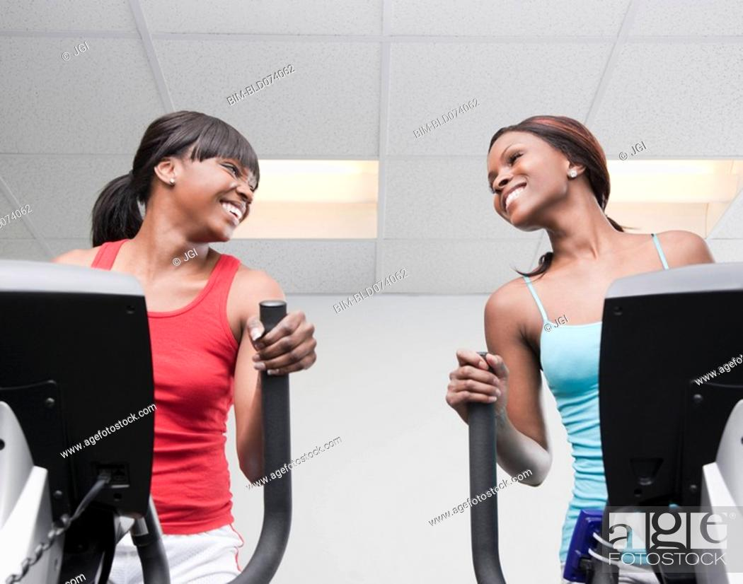 Stock Photo: African women using exercise equipment in health club.