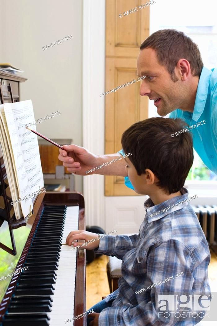 Stock Photo: Father teaching son how to play the piano.