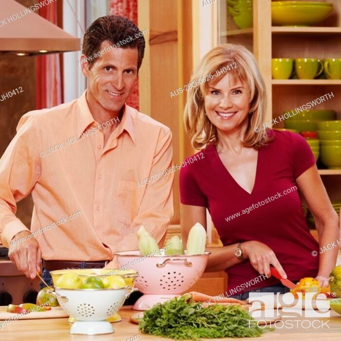 Stock Photo: Portrait of a mature couple cutting vegetables and smiling.