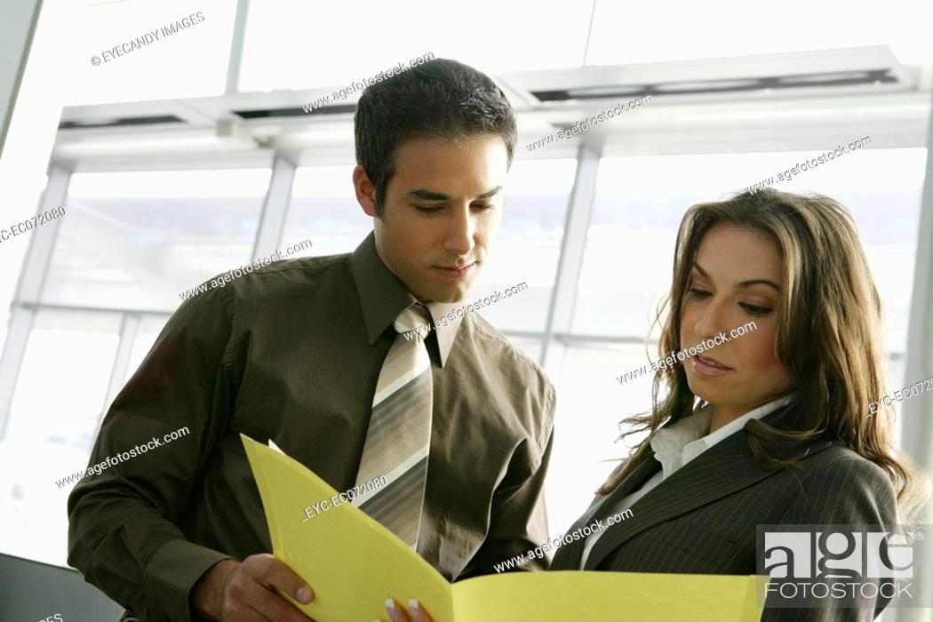 Stock Photo: Businesspeople looking at paperwork in airport.