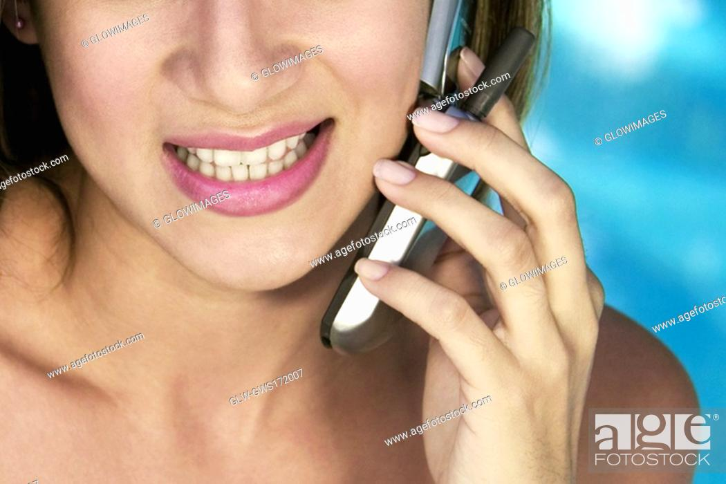 Stock Photo: Close-up of a young woman using a mobile phone and smiling.