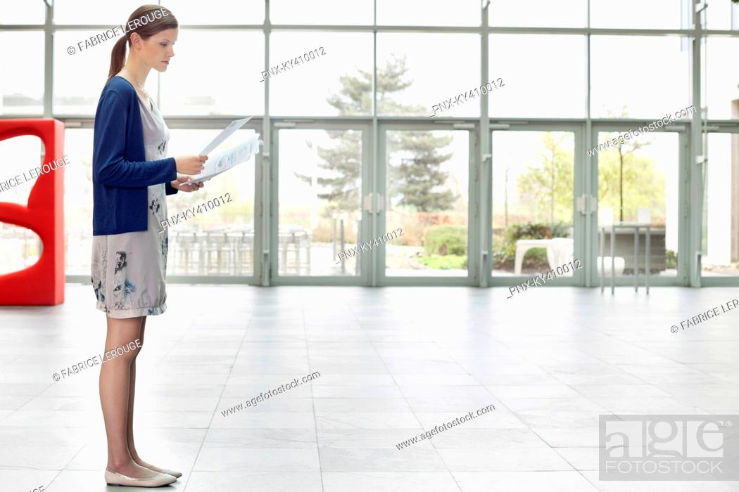 Stock Photo: Businesswoman holding documents and standing in an office lobby.
