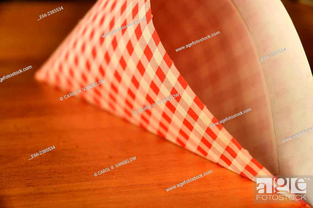 Stock Photo: Red and white checkered paper french fries sack laying on wooden table.