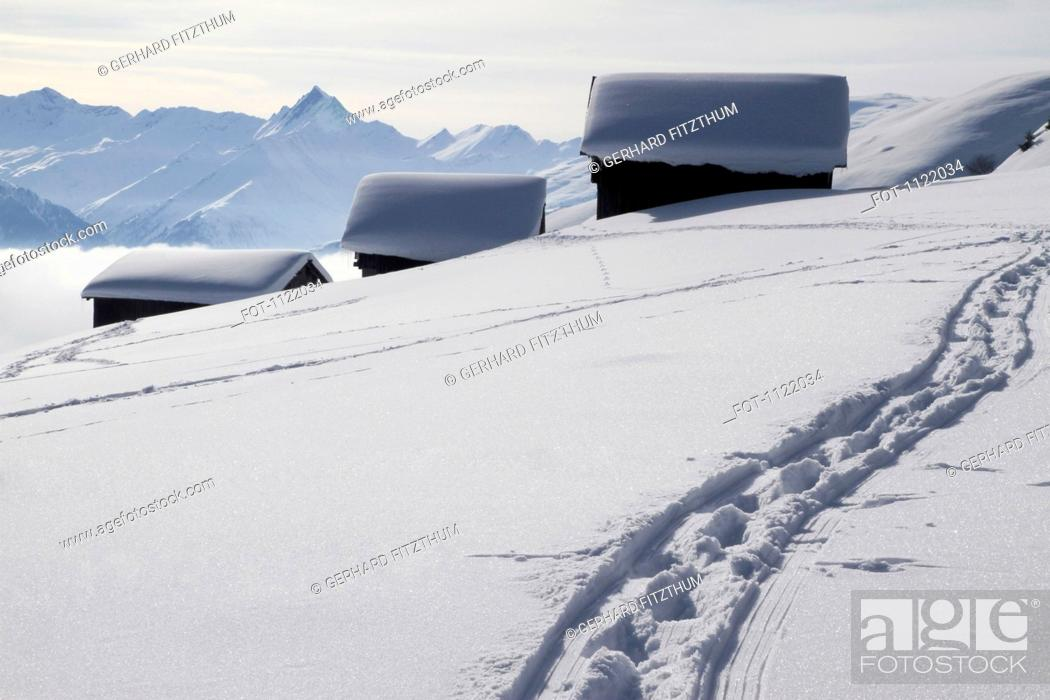 Stock Photo: Foot path leading to three snow-capped log cabins.
