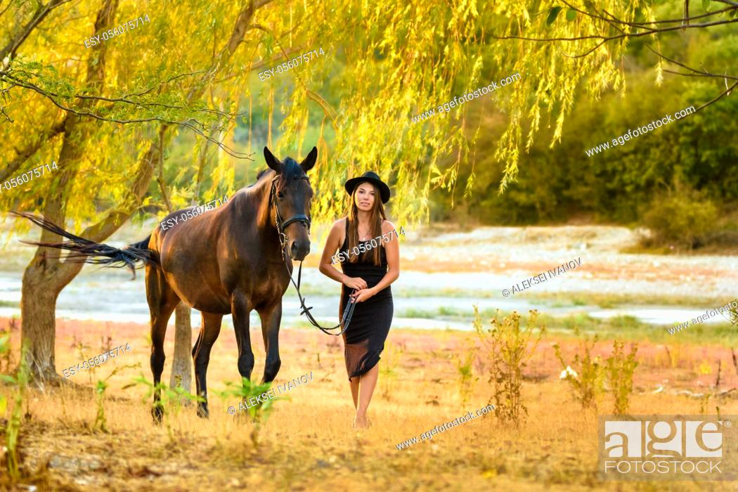 Stock Photo: A girl in a beautiful black dress and a black hat walks with a horse across the field.