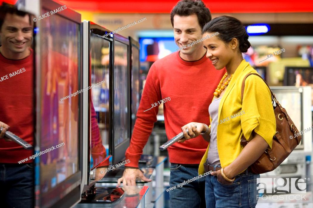 Stock Photo: Young couple shopping for television, smiling, side view.