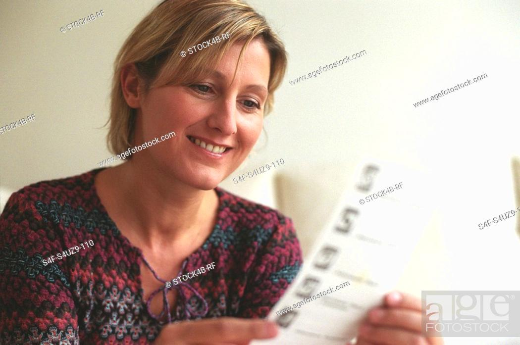 Stock Photo: Blonde Woman reading Game Instructions.