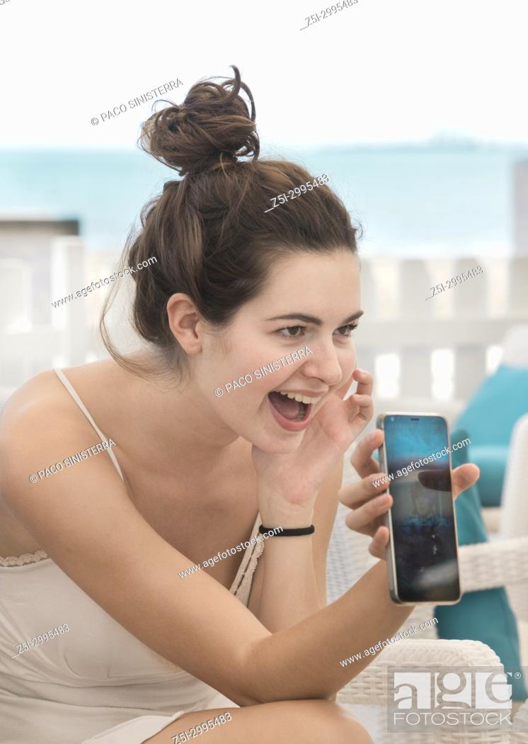 Stock Photo: Young girl showing her cellphone. Benicasim, Spain.