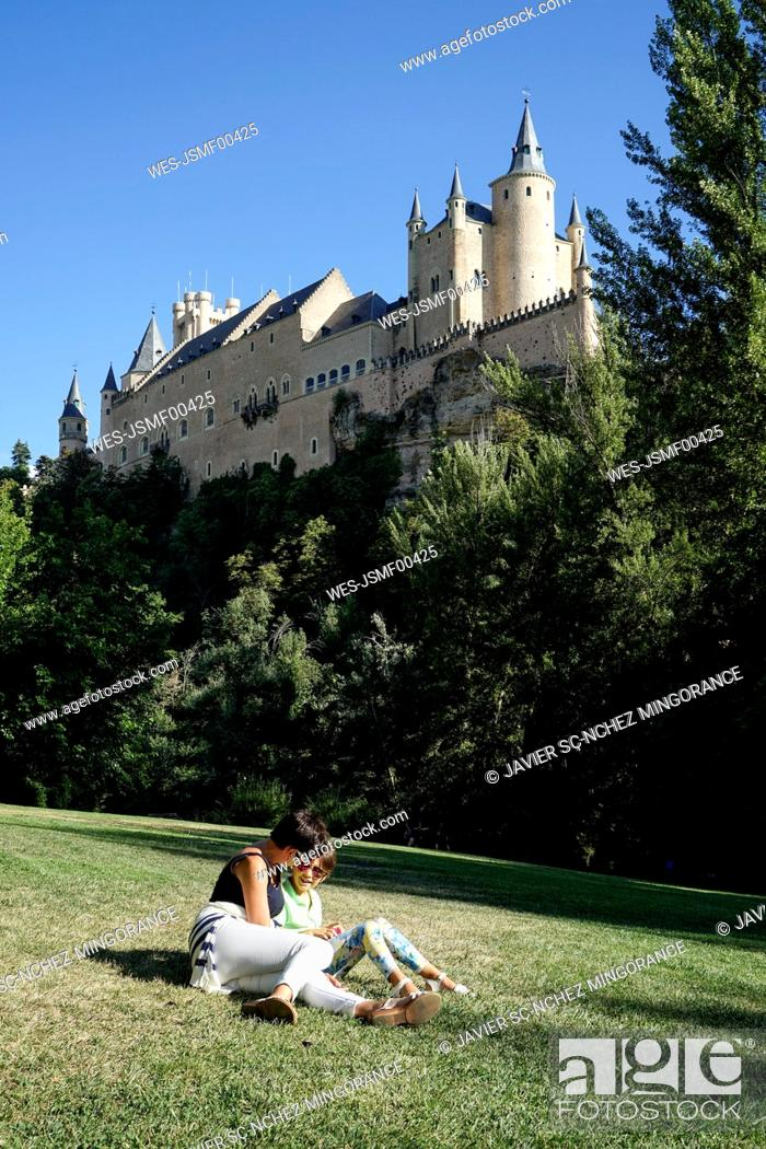 Stock Photo: Spain, Castile and Leon, Segovia, Mother and daughter sitting on grass near to Alcazar of Segovia.