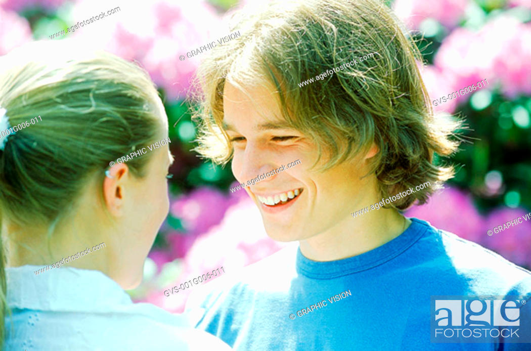 Stock Photo: Young couple standing face to face and talking.