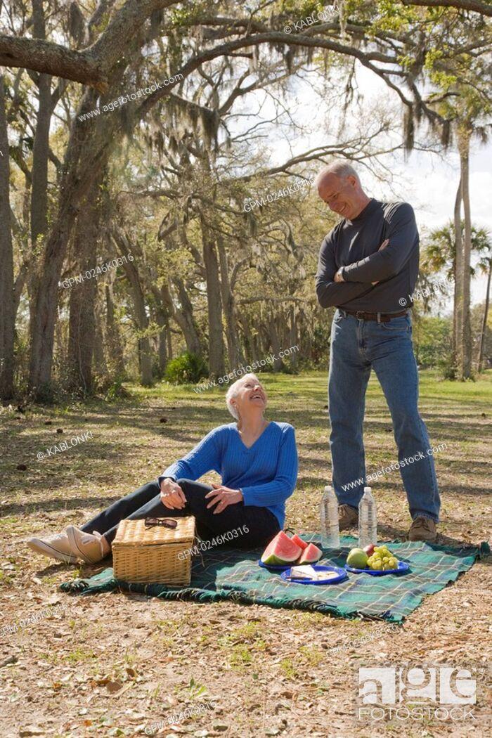 Imagen: Senior couple having picnic in garden, smiling.