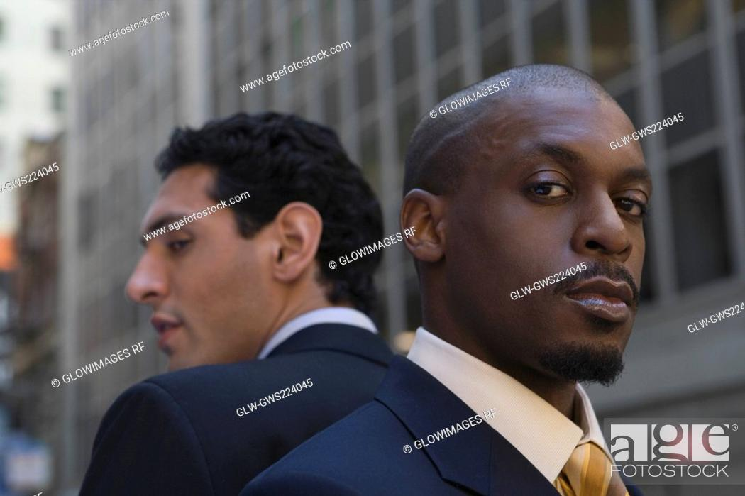 Stock Photo: Close-up of two businessmen back to back.