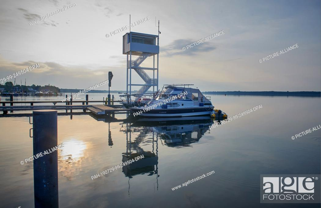 Stock Photo: 29 July 2019, Berlin: A boat lies in front of the water rescue station of the German Lifesaving Society DLRG, while the rising sun is reflected in the Müggelsee.