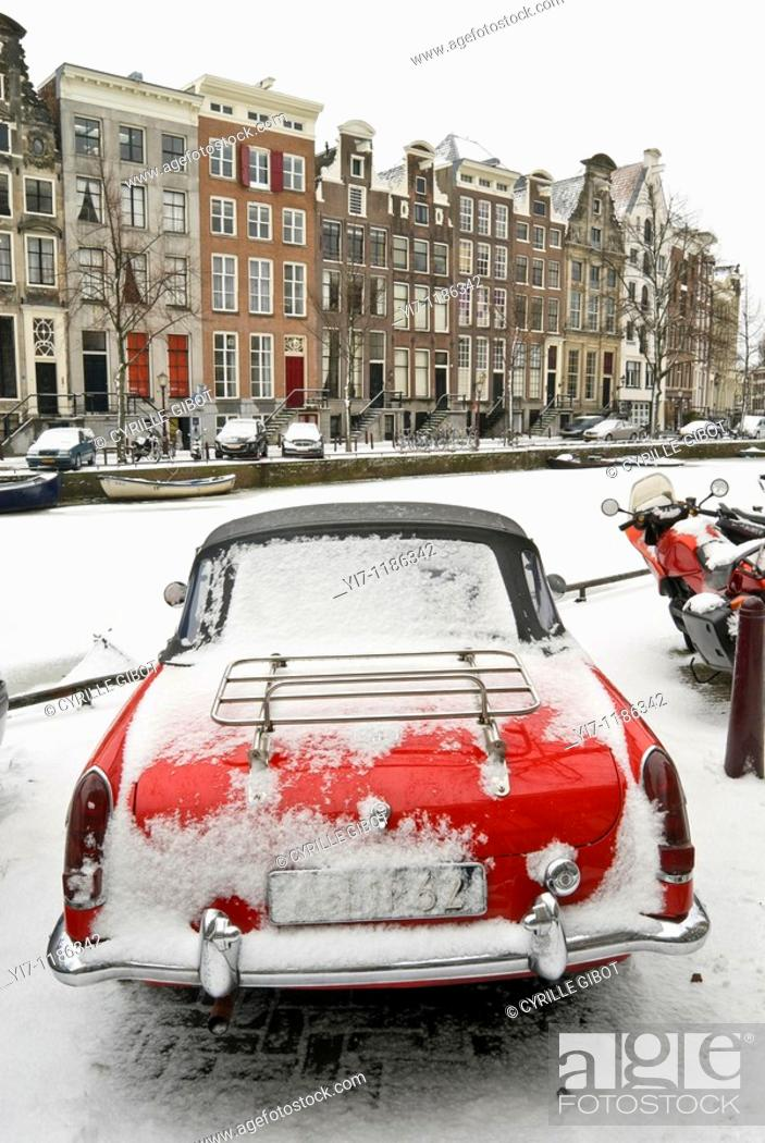 Stock Photo: Red sports car by frozen Keizersgracht canal, Amsterdam, the Netherlands.