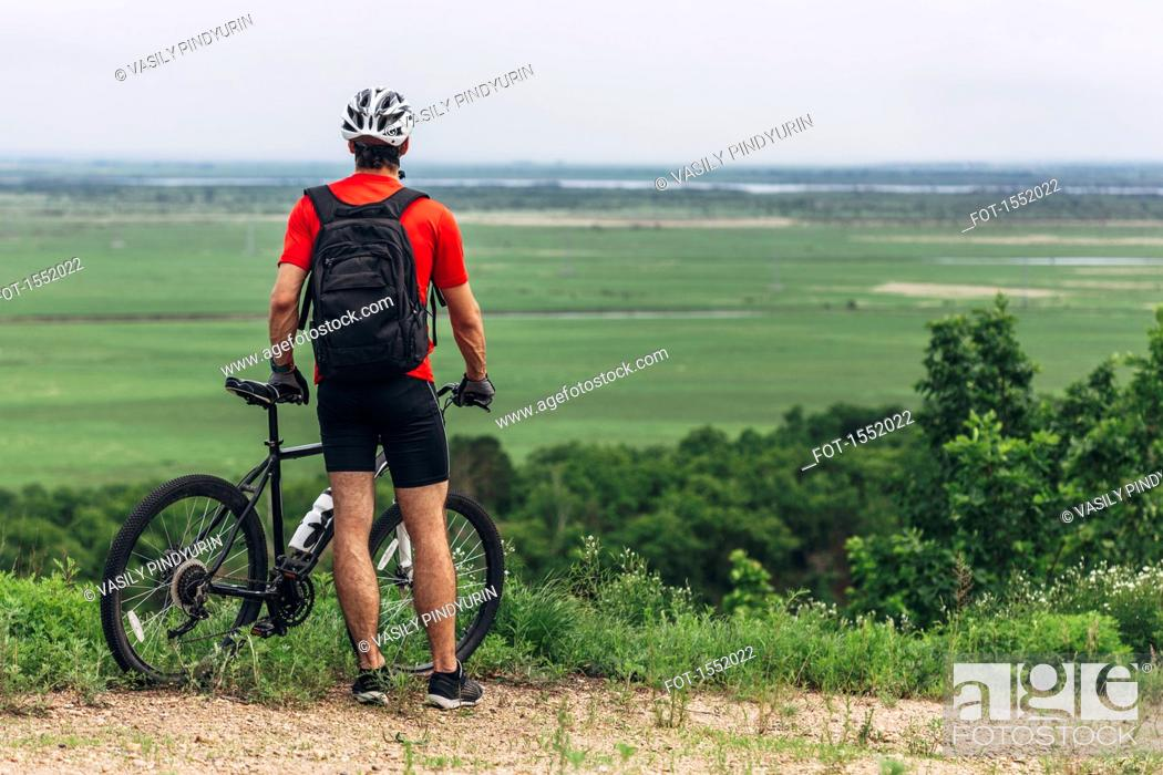 Stock Photo: Rear view of man with mountain bike standing on hill.