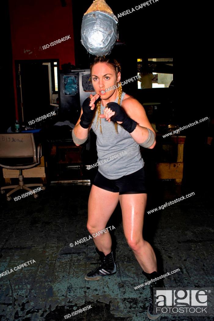 Stock Photo: Female boxer training in gym, punching punchball.