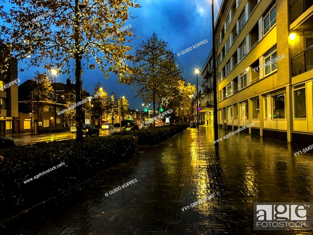 Imagen: Tilburg, Netherlands. Down town residential street with apartment buildings, sidewalk and lights, during a fall season rainy evening at dusk.