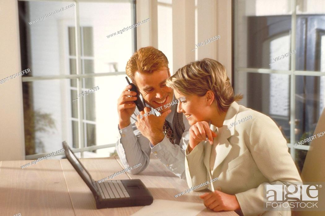 Stock Photo: indoor, blond couple mid of 30 sits laughing at the table near the window in front of a notebook, whiles the man is making a phone call  - GERMANY, 26/02/2005.