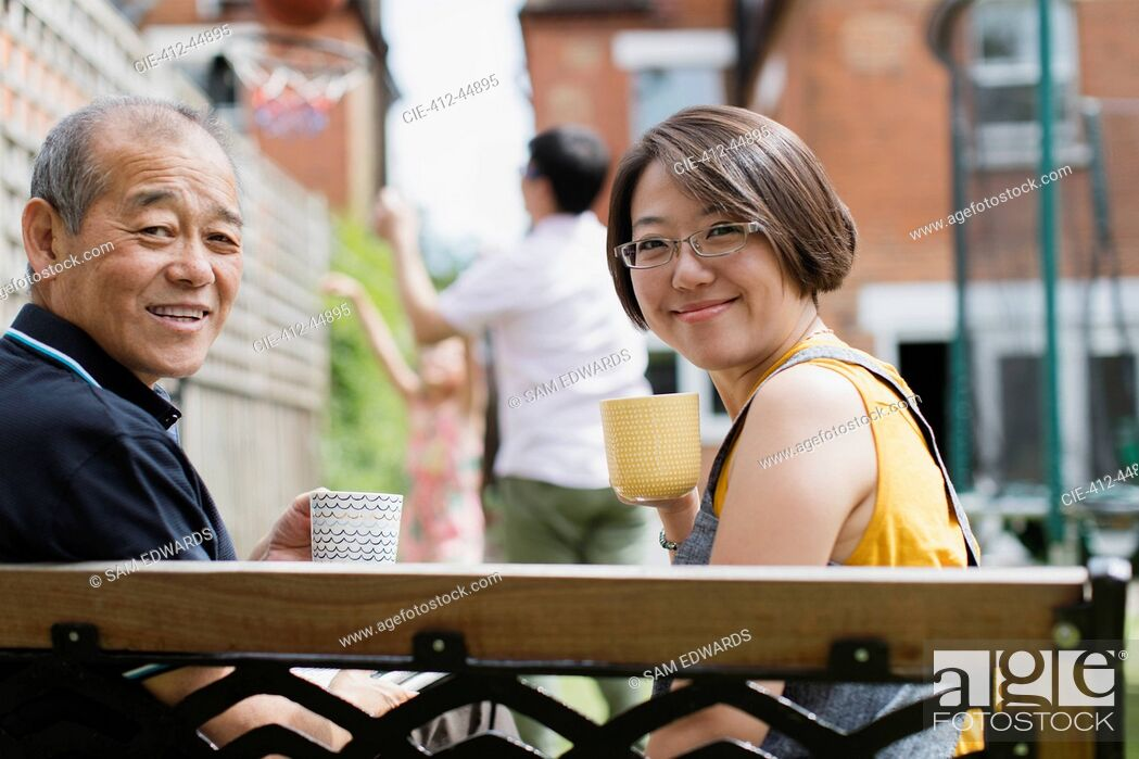 Stock Photo: Portrait smiling daughter and senior father drinking tea on bench in yard.