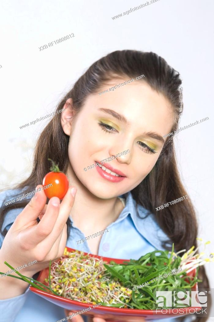 Stock Photo: Young woman eating salad.