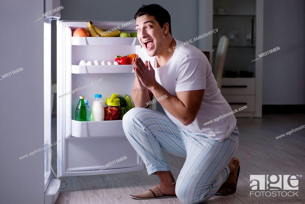 Stock Photo: Man at the fridge eating at night.