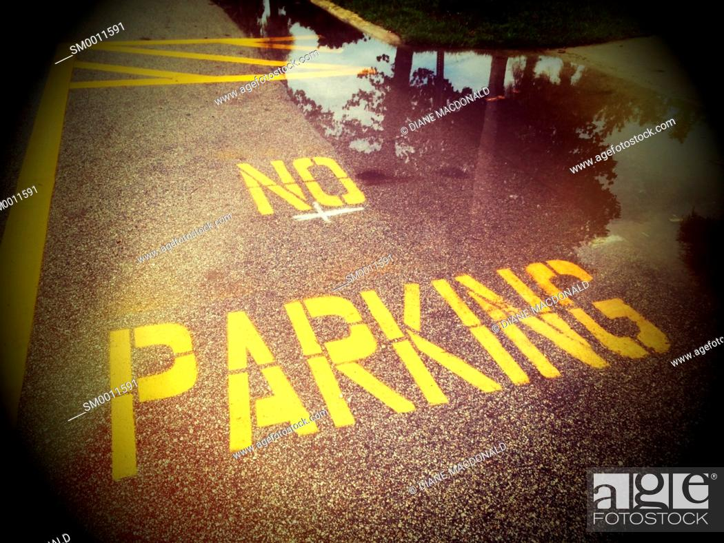 Stock Photo: No Parking painted on road next to a puddle of water, Jacksonville Beach, Florida.