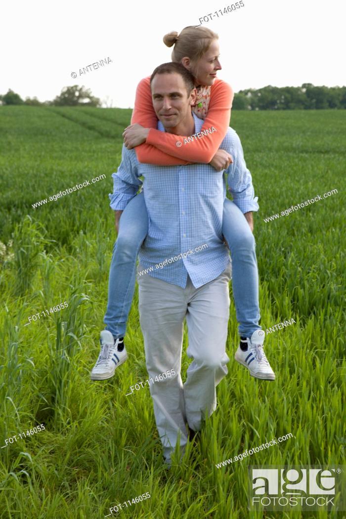 Stock Photo: A man giving his girlfriend a piggy back ride through a field.