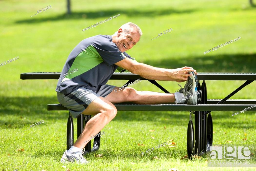 Stock Photo: Mature man stretching on park bench, smiling, portrait.