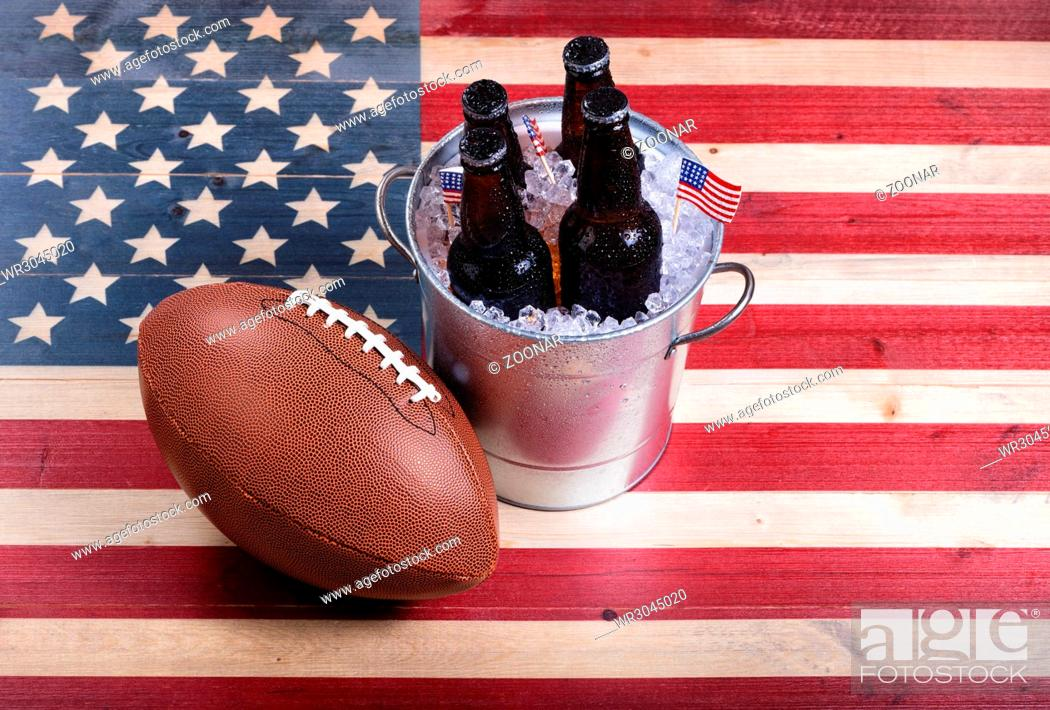 Photo de stock: American football and ice cold beer on rustic wooden USA flag.