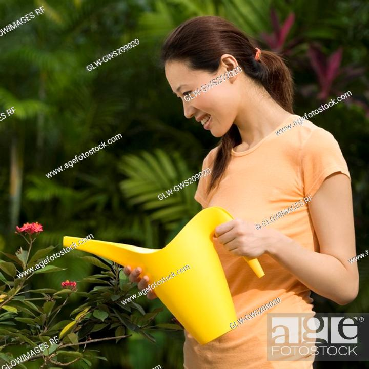 Stock Photo: Young woman watering plant with a watering can and smiling.