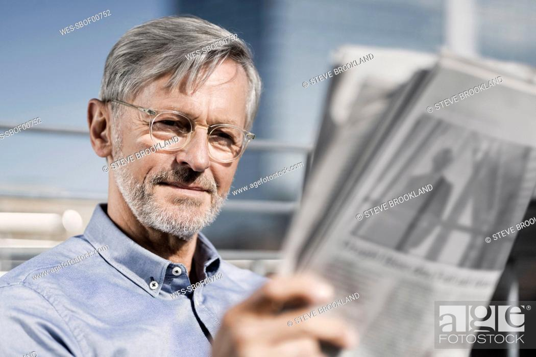 Stock Photo: Grey-haired man reading newspaper.