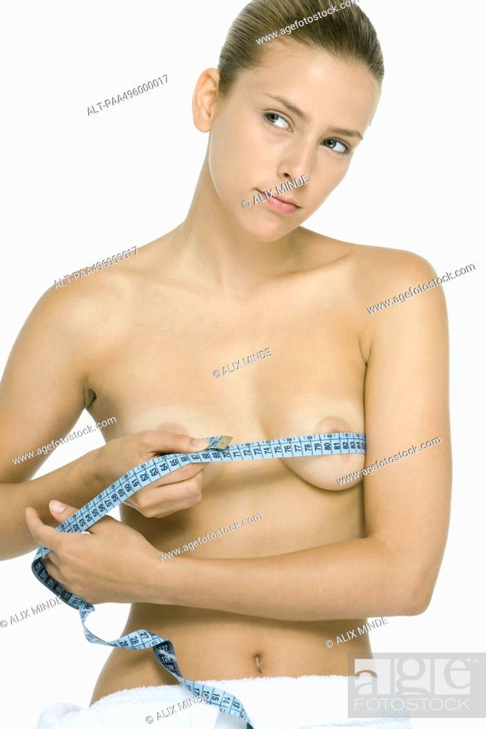 Stock Photo: Woman holding measuring tape around chest, looking away.