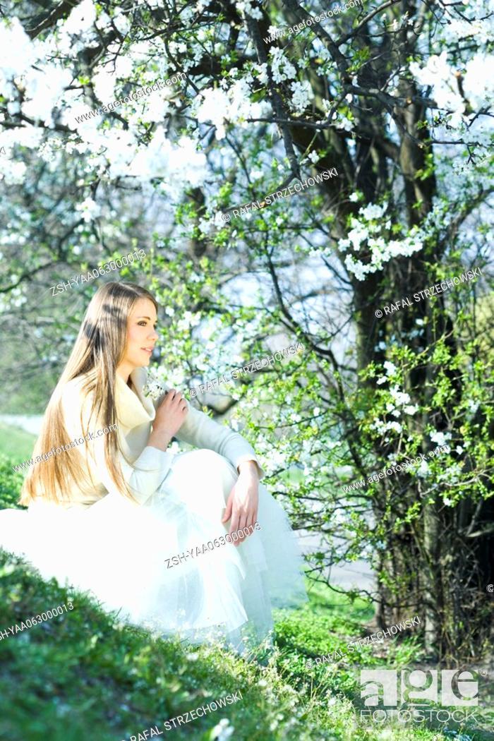 Stock Photo: Teenage girl sitting outdoors, holding flowers, looking away.