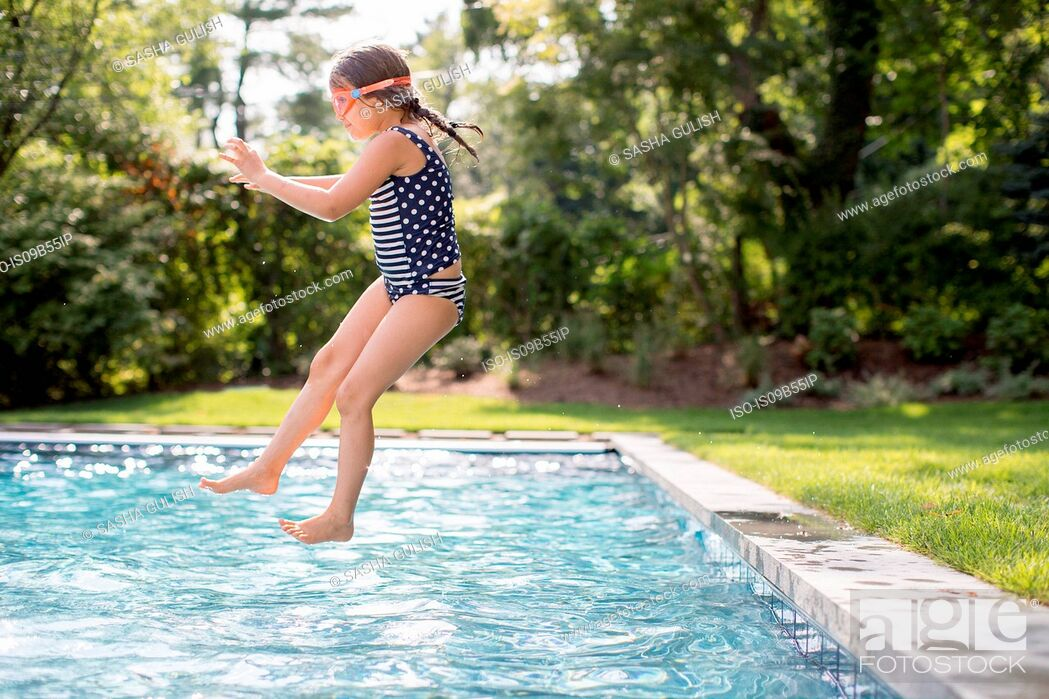 Stock Photo: Girl jumping into outdoor swimming pool.