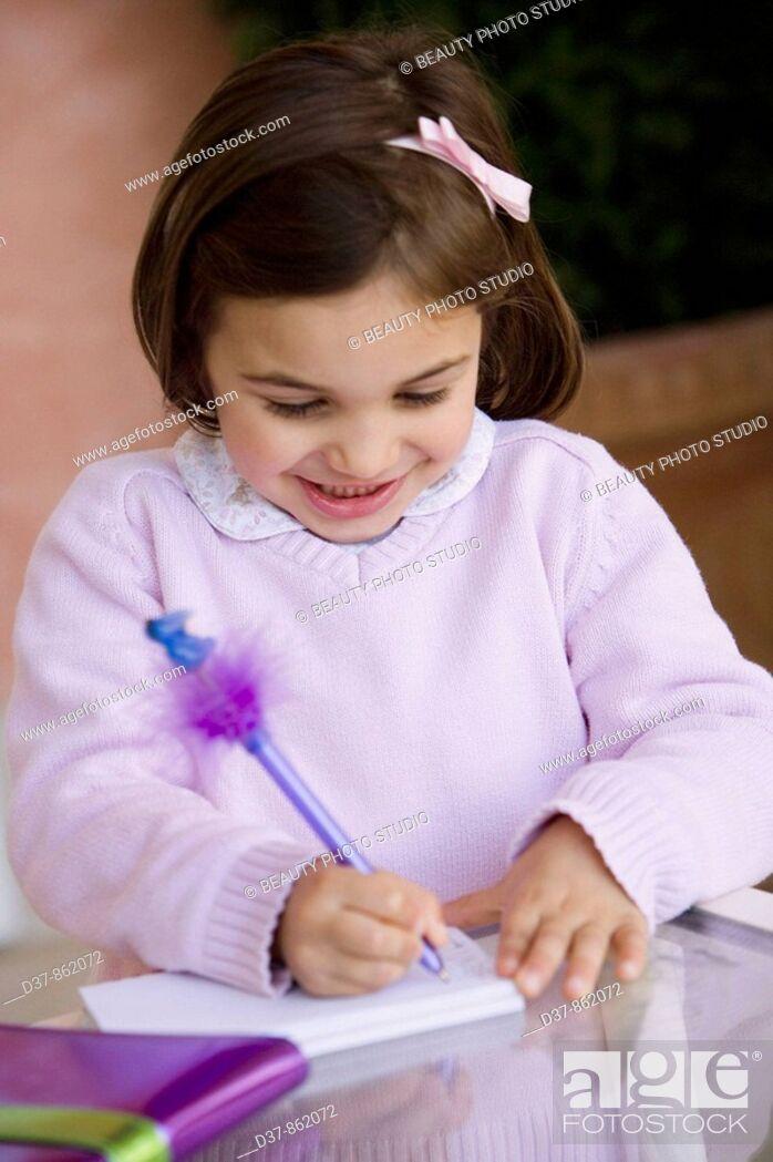 Imagen: Little girl writing on a notebook.