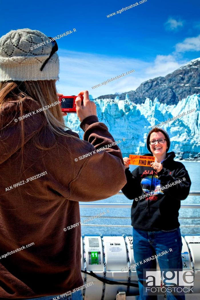 Stock Photo: A young woman is taking a picture of her friend in front of Margerie Glacier on a tour boat, Tarr Inlet, Glacier Bay National Park & Preserve, Southeast Alaska.