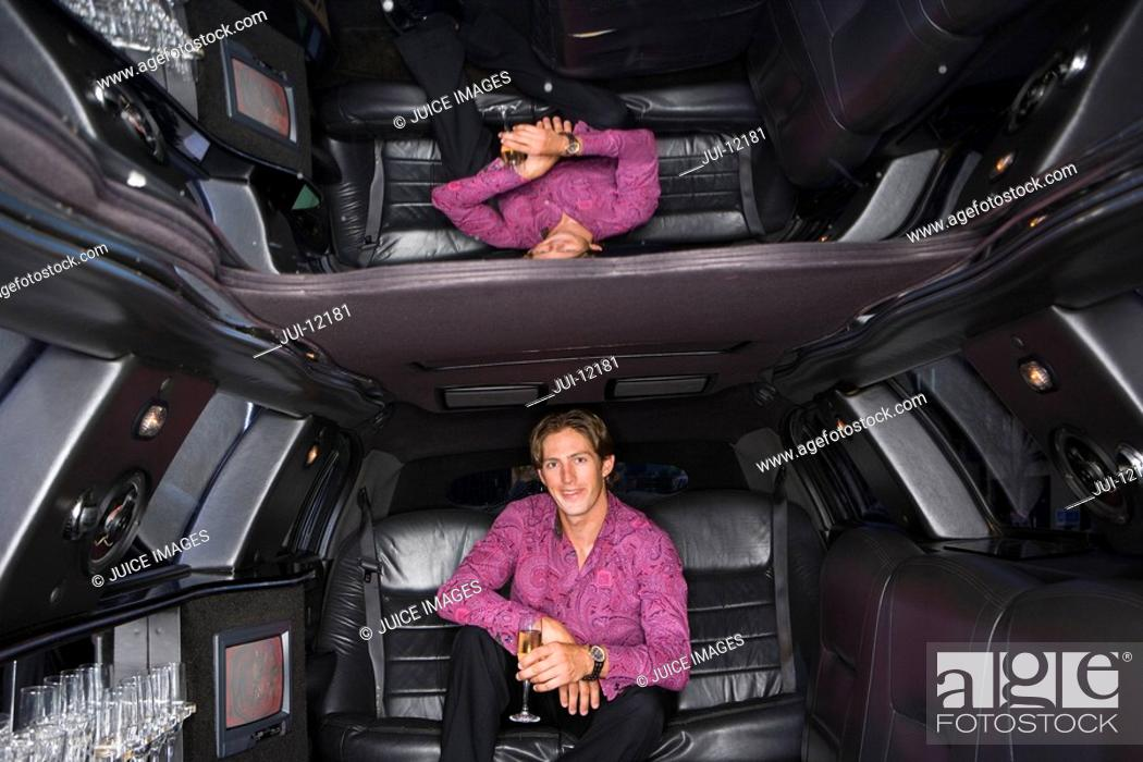 Stock Photo: Young man with drink in limousine, reflection in ceiling, smiling, portrait.