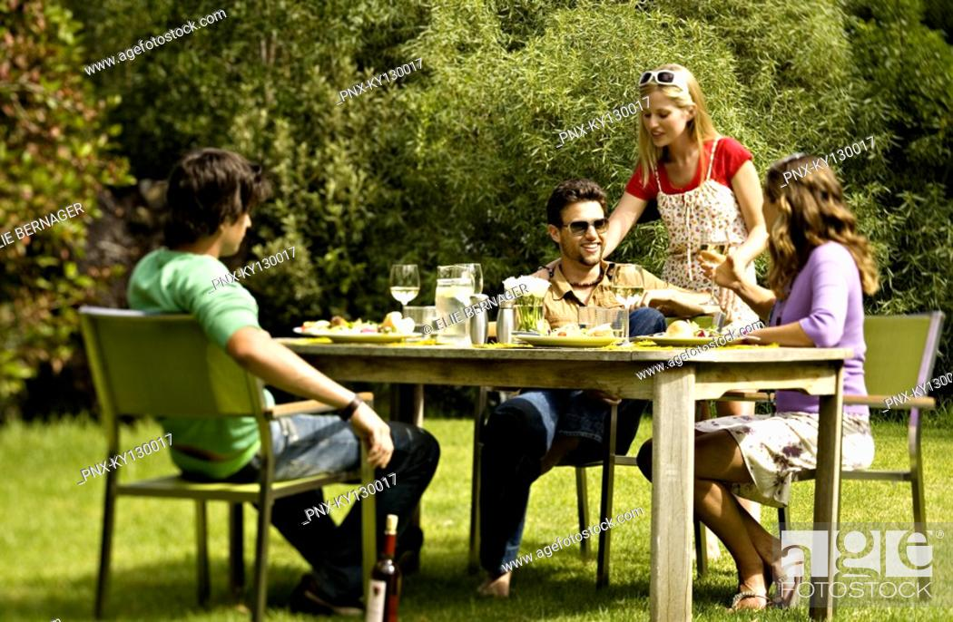 Stock Photo: 2 young couples sitting at garden table.