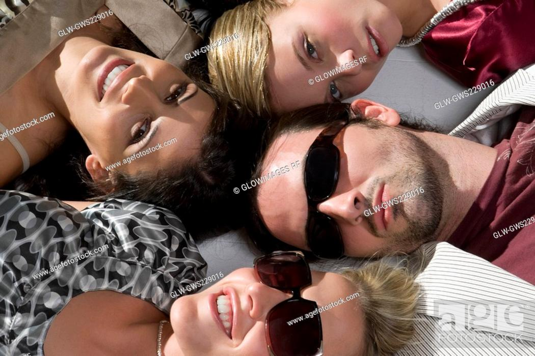 Stock Photo: Close-up of a young man with three young women lying down.