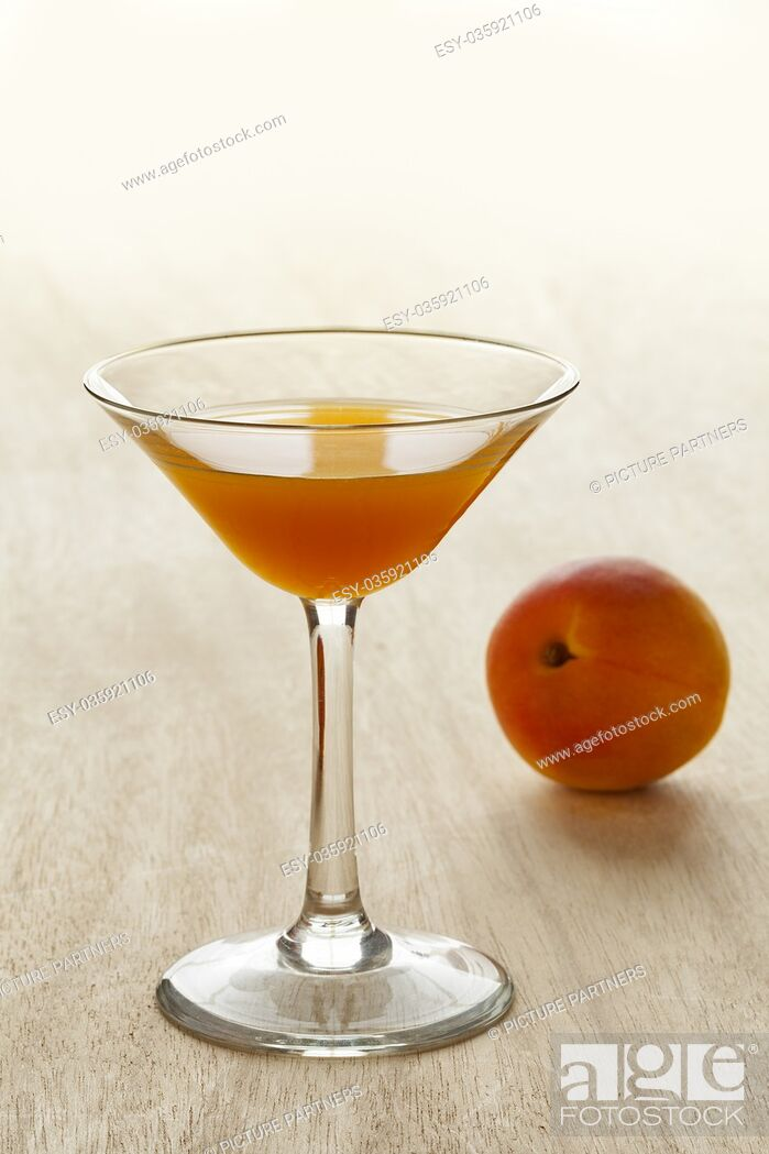 Stock Photo: Glass of apricot liqueur and fresh fruit on the background.