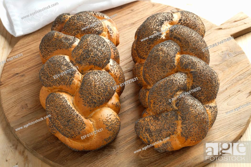Photo de stock: Two whole fresh Challah breads with poppy seeds on a cutting board.