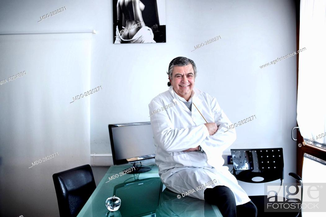 Stock Photo: The professor and world famous plastic surgeon Marco Gasparotti posing seated on the desk for a photocall at his medical practice.