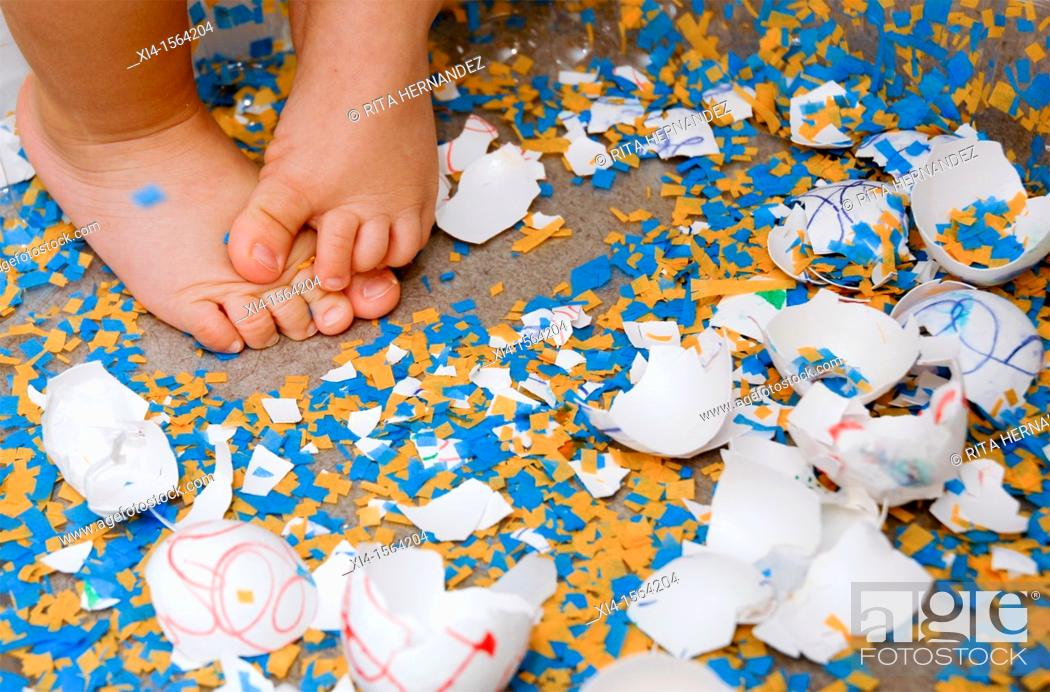 Stock Photo: Close up of baby feet in the middle of broken easter eggs.