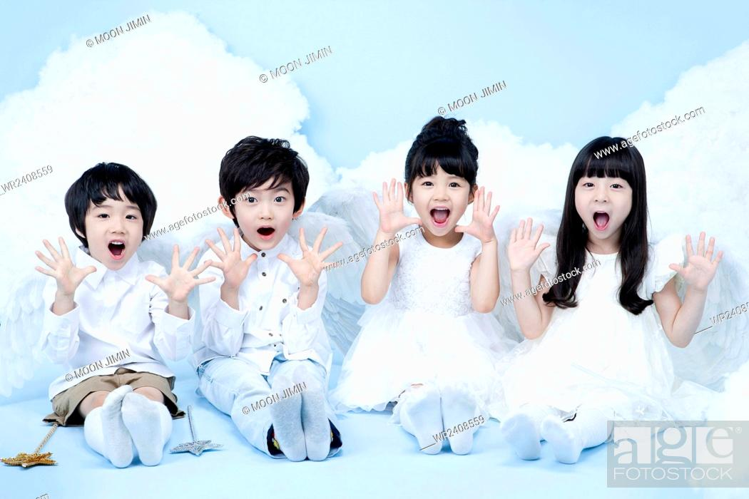 Stock Photo: Four children in angel costume seated together in surprise in the background representing heaven.
