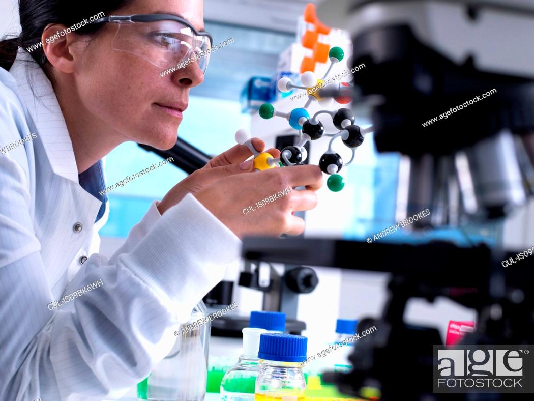 Stock Photo: Scientist understanding structure of chemical compound using molecular model.
