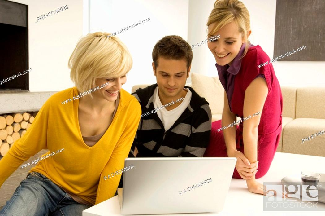 Stock Photo: Young man with two young women looking at a laptop.