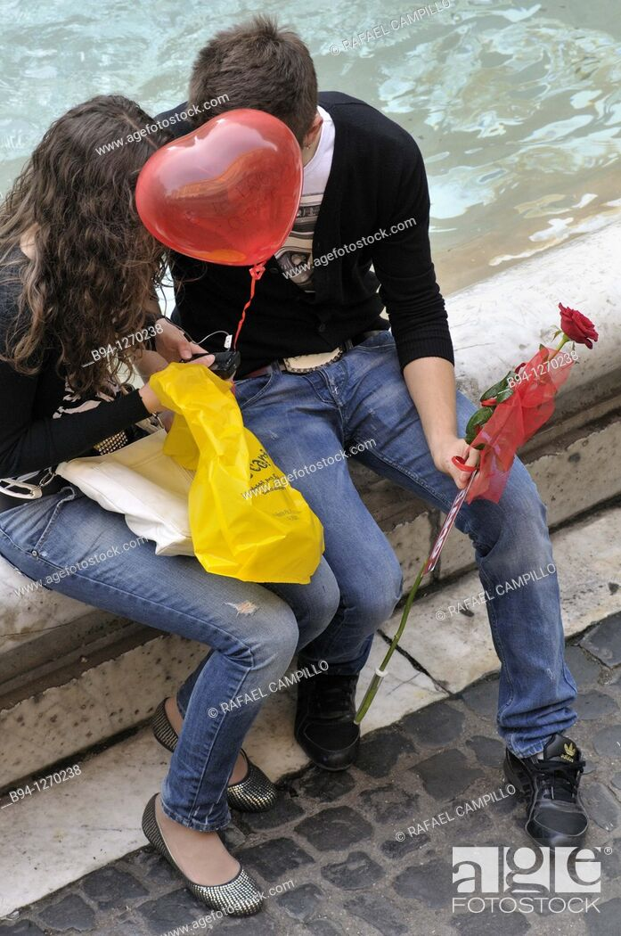 Stock Photo: Couple in love with red balloon in the shape of heart and a red rose. Trevi Fountain. Rome, Italy.